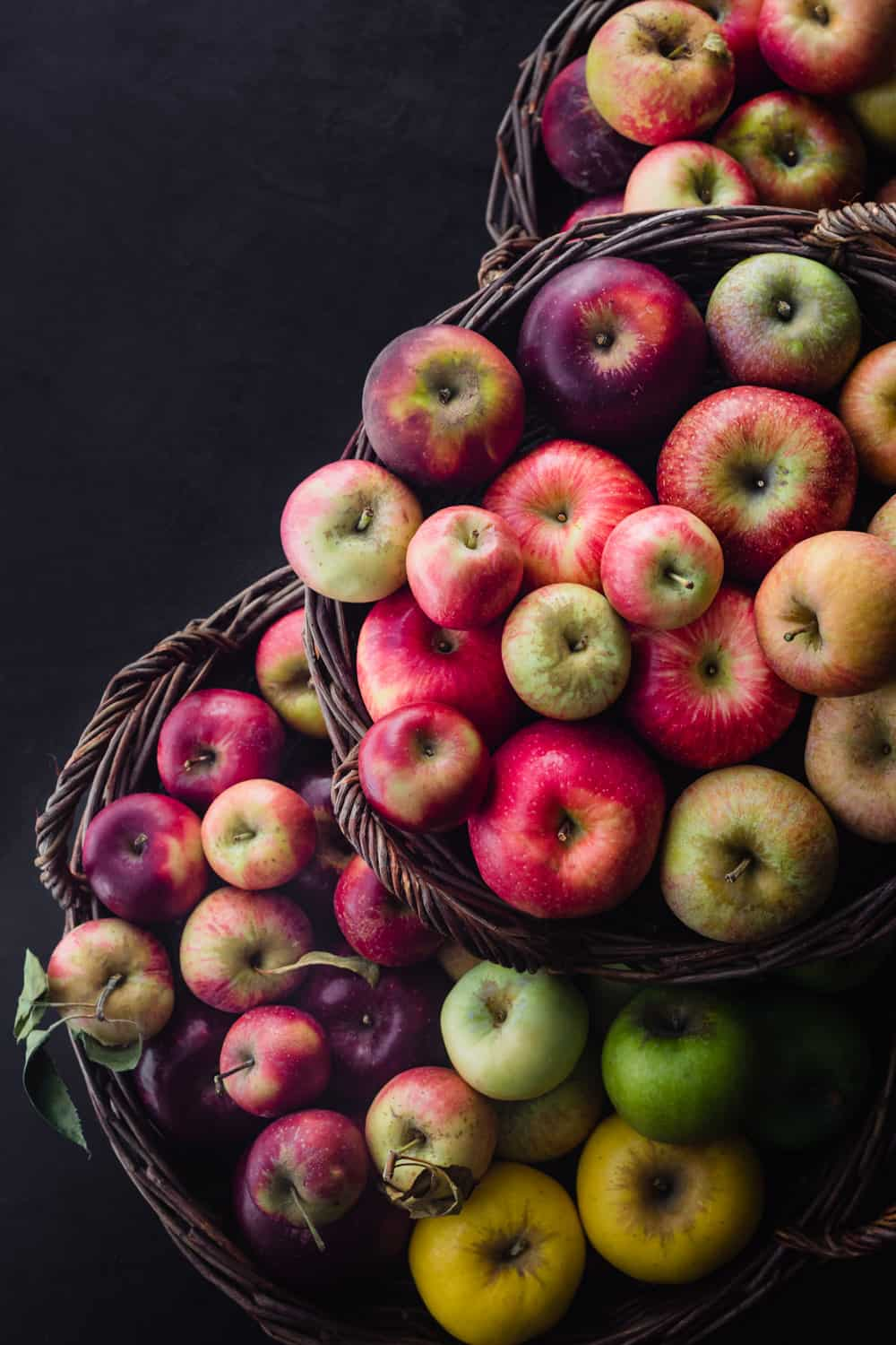 3 different baked filled with fresh apples in all colors of the rainbow; overhead on a black background.
