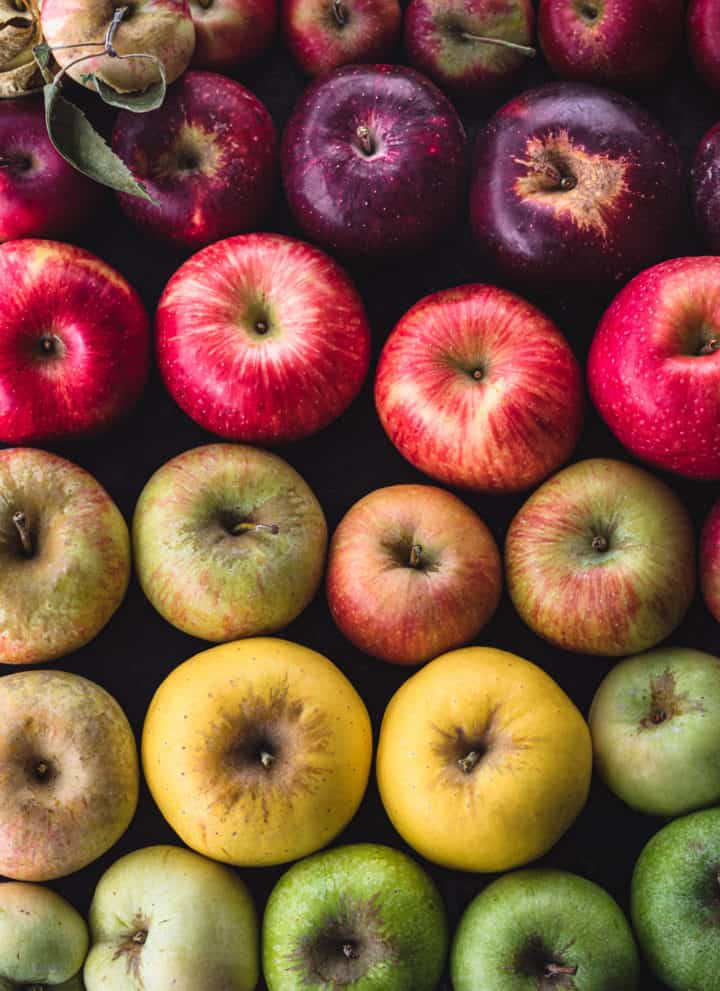 Apples arranged like a rainbow! There's red, purple, pink, yellow, green and hues in between; on a black background.