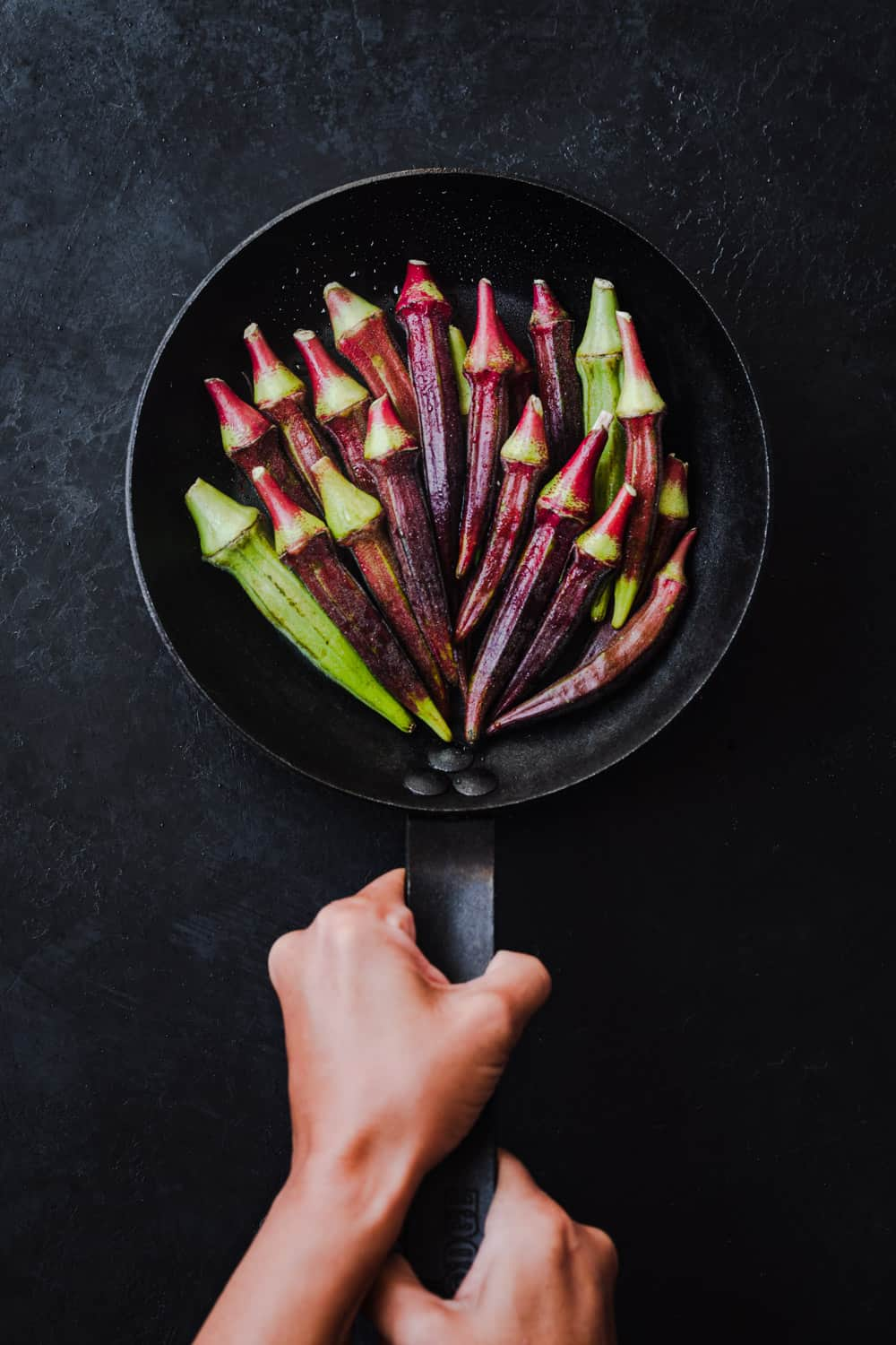 Fresh red okra pods in a black pan held by Daniela Gerson; overhead shot on a black background.
