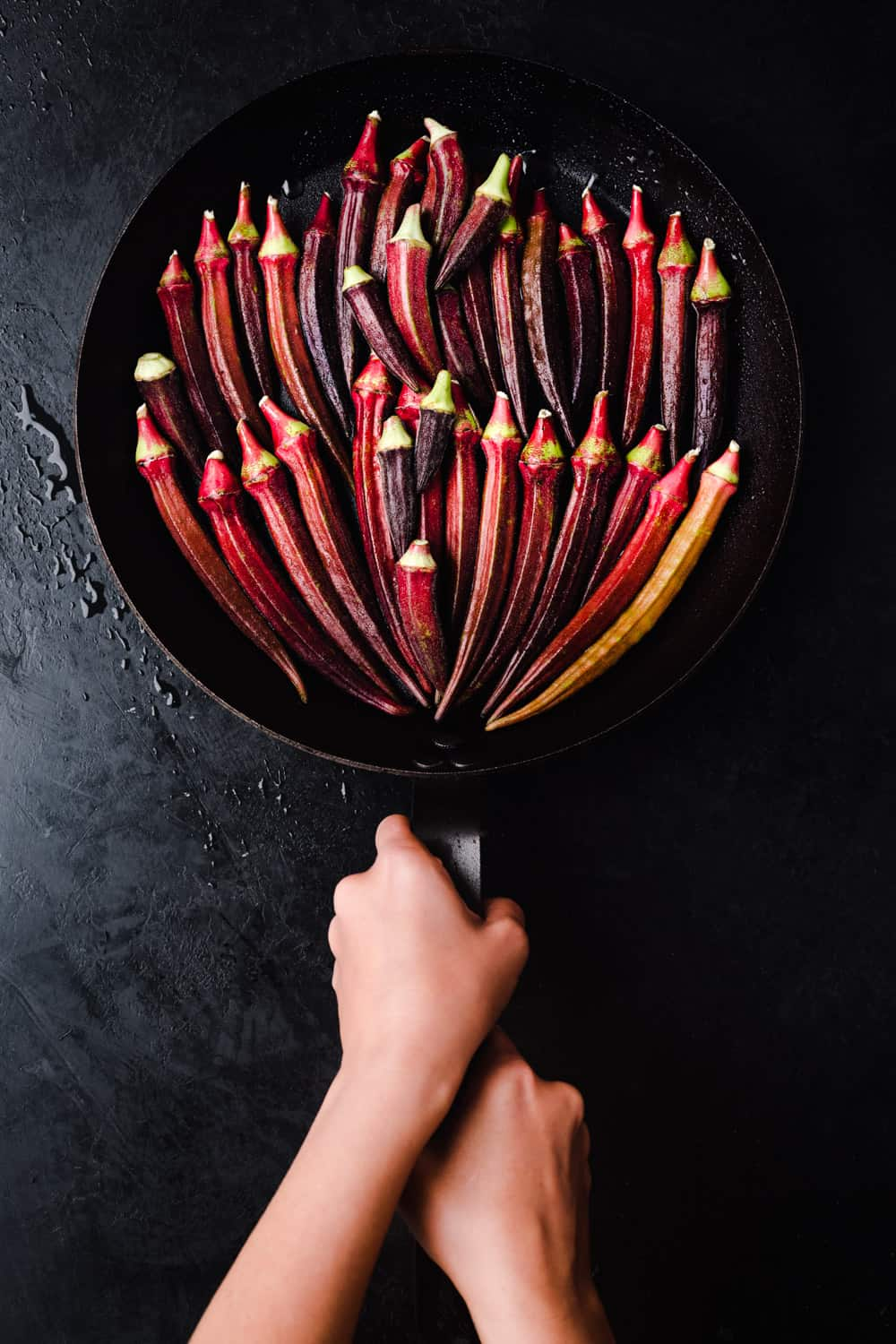 Big plan pan filled with red okra; Daniela Gerson's hands in frame holding pan; overhead shot.