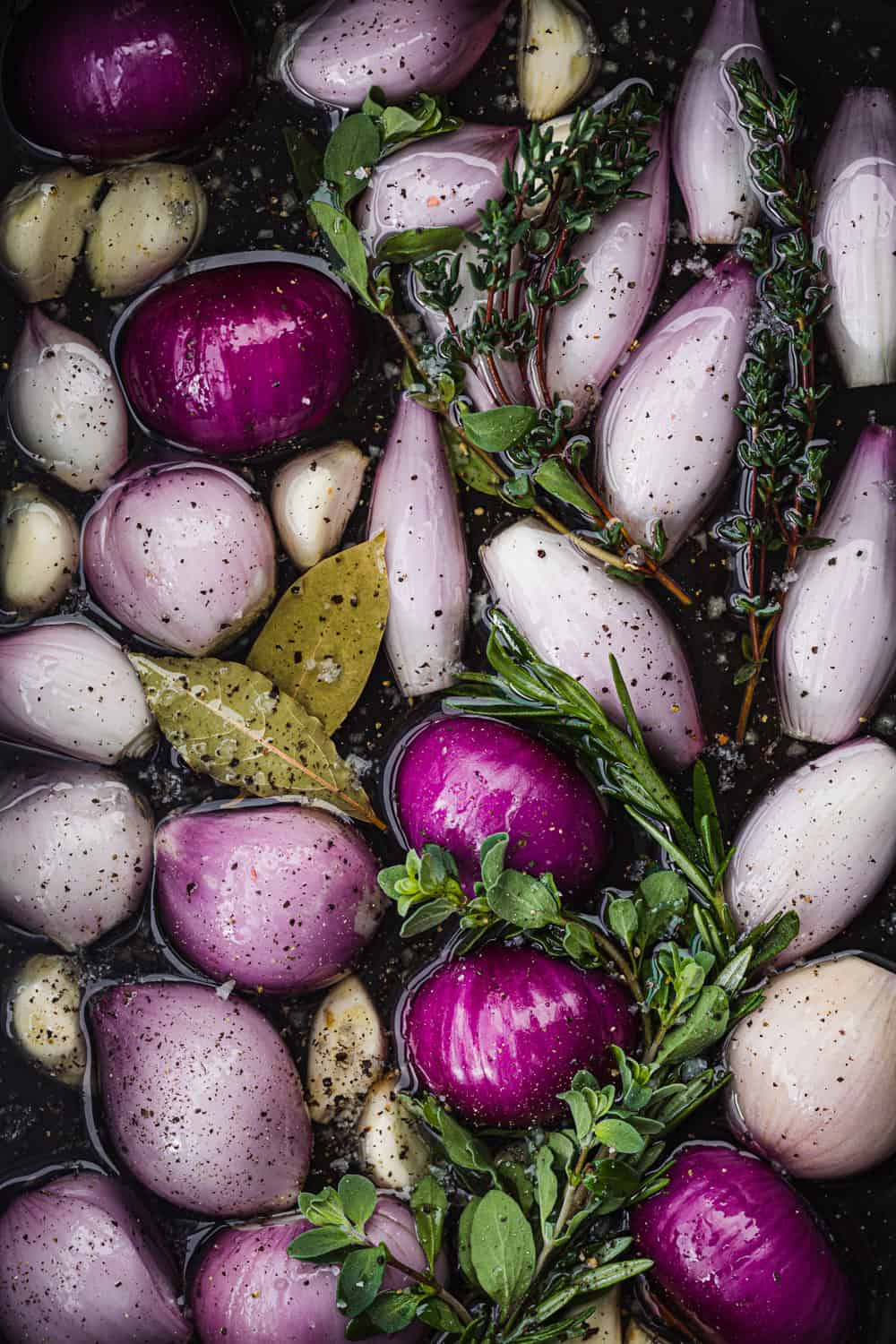 Shallot confit in the making! Whole and halved raw shallots submerged in olive oil with garlic, bay leaves, fresh herbs, salt and pepper; overhead shot.