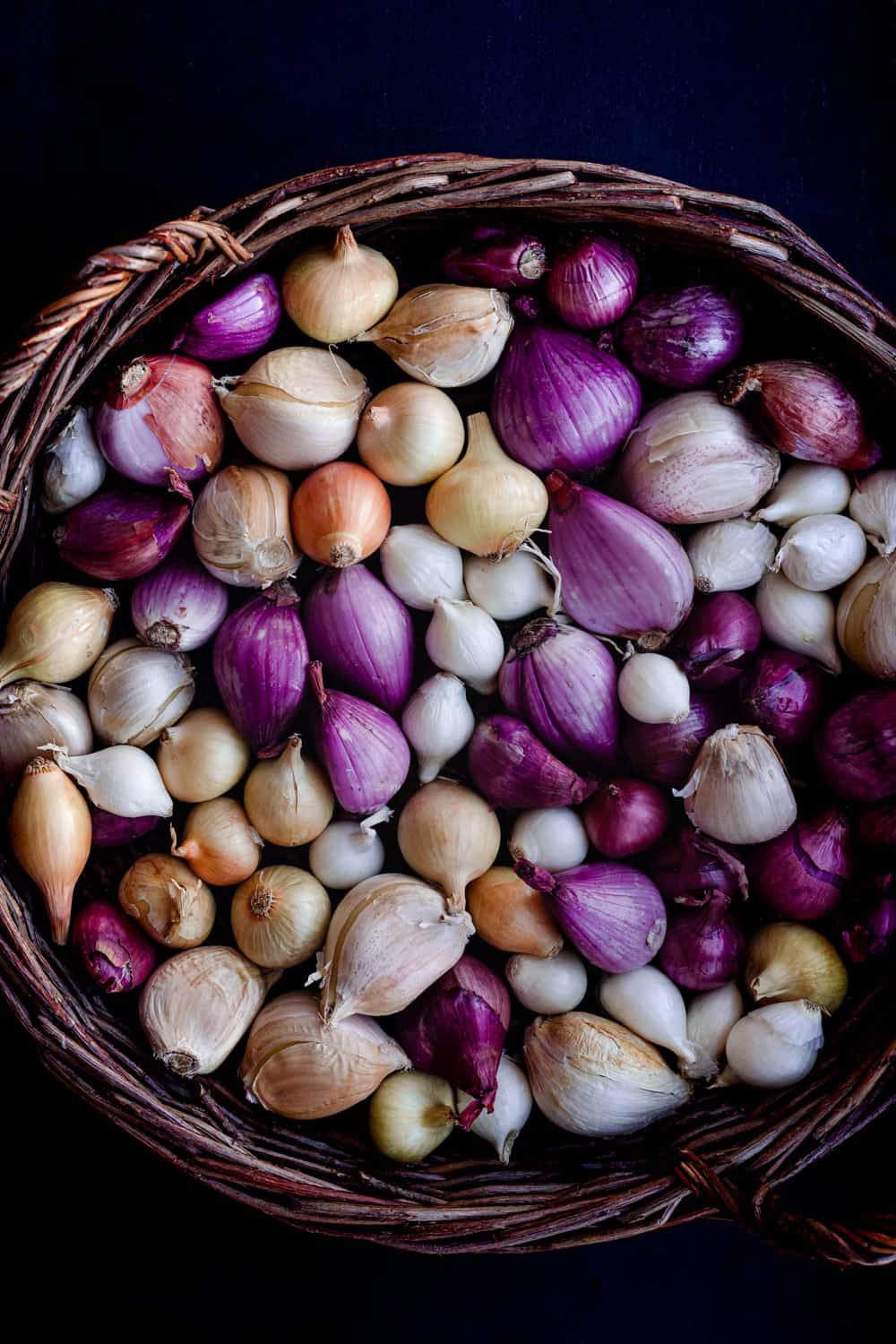 Raw allium ingredient shot; lots of different colors of shallots, onions and garlic are in a woven basket; overhead shot on a black background.