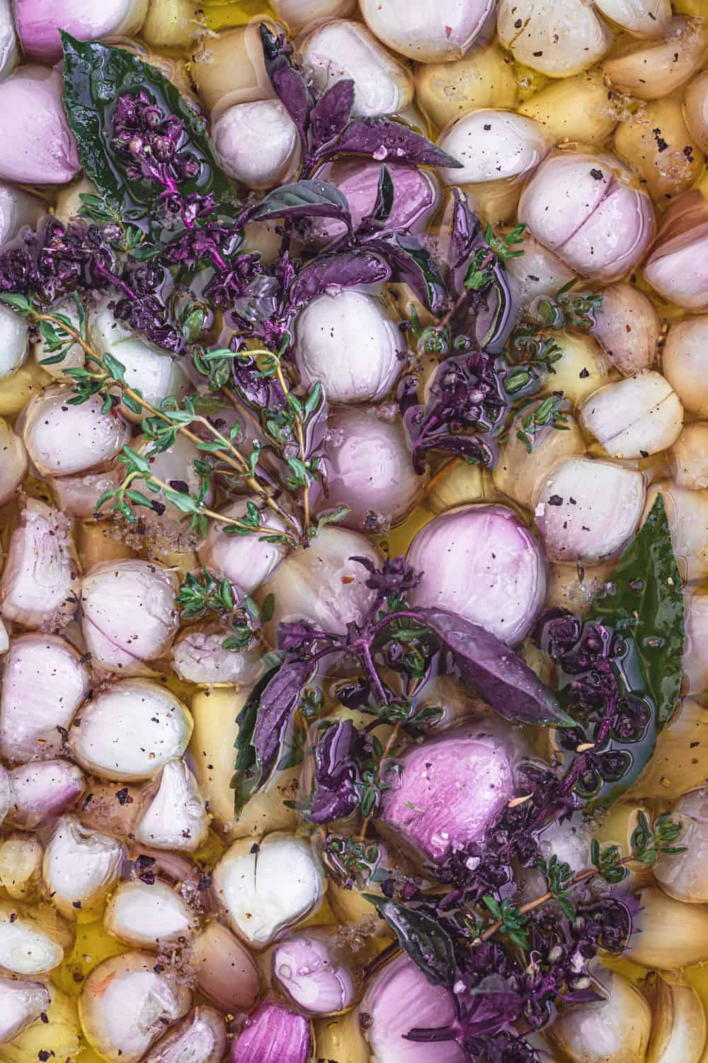 In process shot of shallots submerged in olive oil with fresh herbs, salt and pepper; pre-oven, in an oven proof dish and overhead shot.