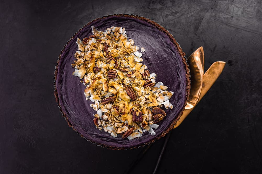 Purple sweet potato pie on a black background with gold utensils in the frame.