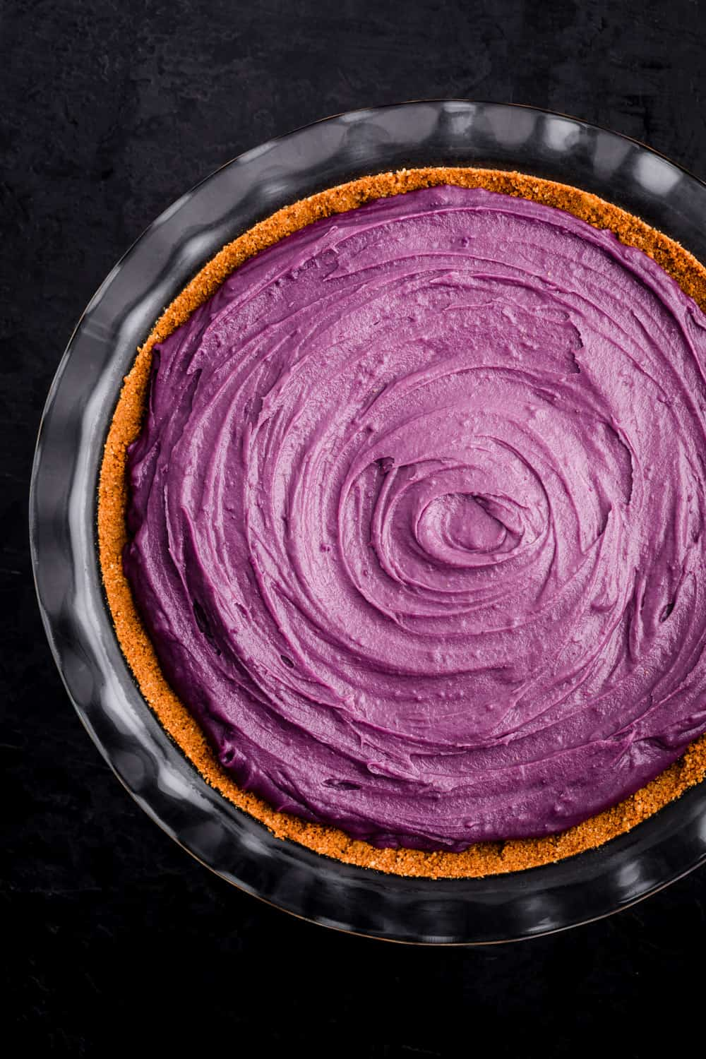 Purple sweet potato pie all ready to be baked in oven; filling has been poured into pie crust onto a pie plate; overhead shot on a black background.