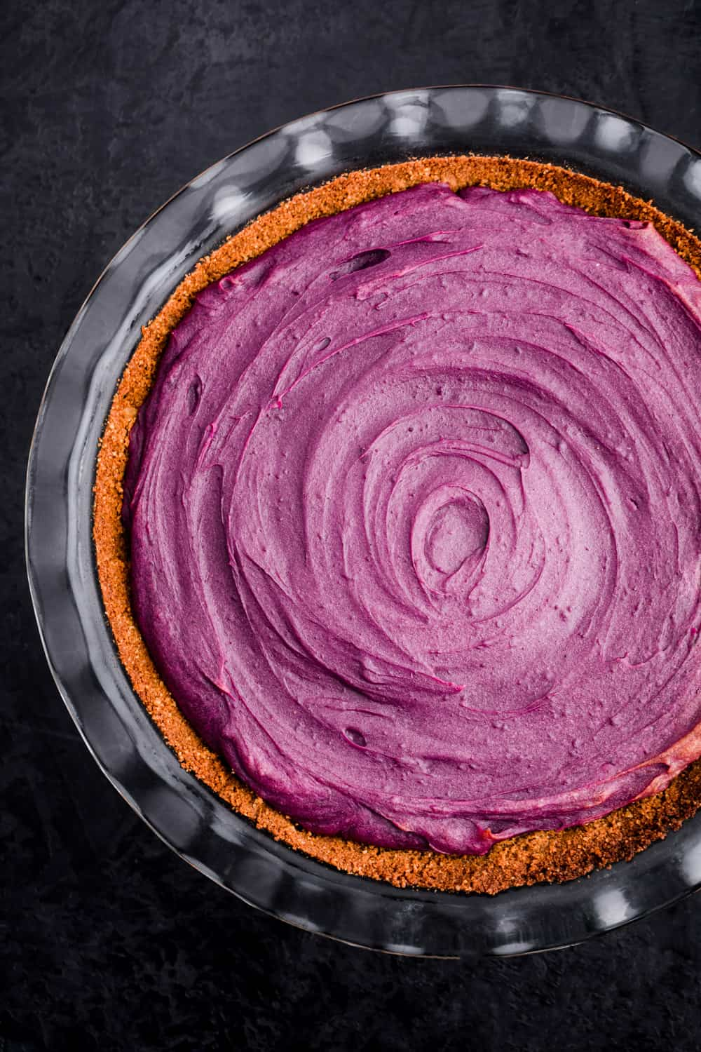 Purple sweet potato pie just out of oven and ready for pecan streusel topping; overhead shot on a black background.