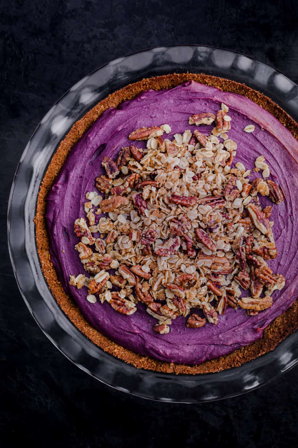 Purple sweet potato pie topped with pecan streusel and all done! Just out of oven; overhead shot on a black background.