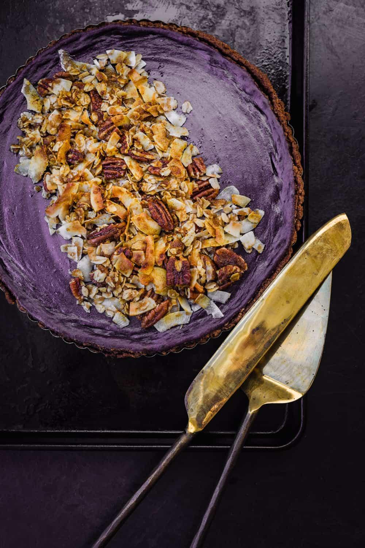 Purple sweet potato pie on a black baking sheet with gold serving utensils, overhead shot.