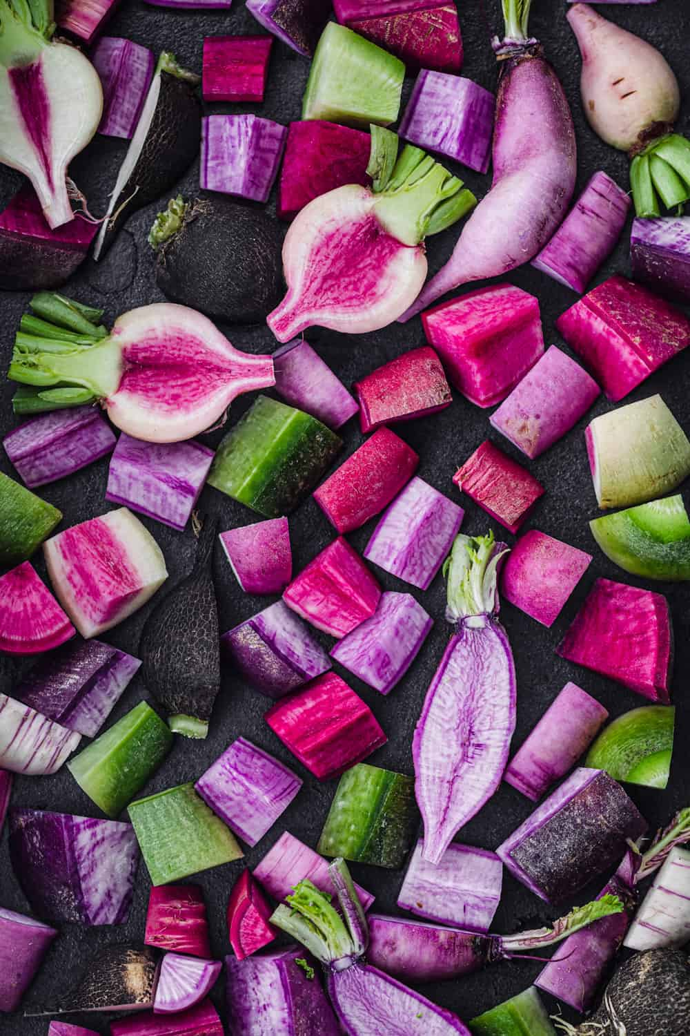 vibrantly colorful and raw radishes cut into bite size pieces on a roasting pan; there's pink, purple, green and black radishes; overhead shot