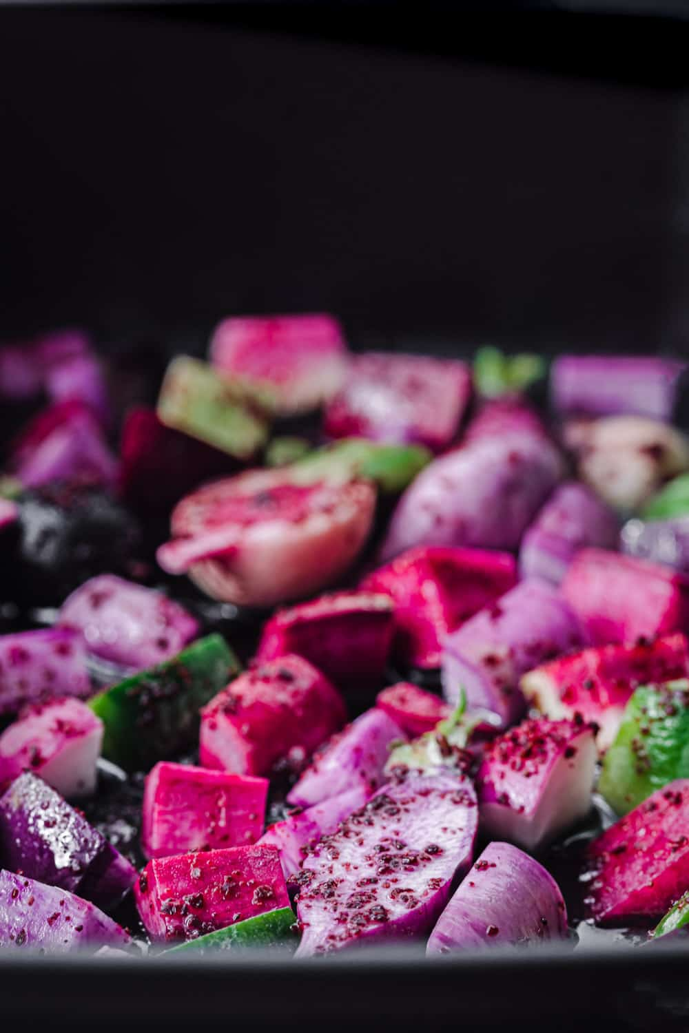 side angle and close up shot of colorful sumac tossed radishes, cut into pieces on a roasting pan and ready to go into the oven.