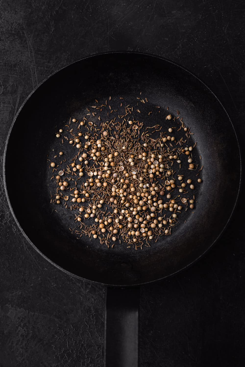 whole coriander and cumin seed, toasted in dry black cast iron skillet on a black background; overhead shot.