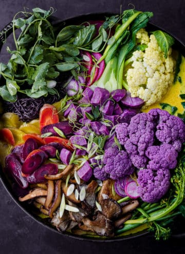 Turmeric Curry Noodle Soup in a large cast iron dutch oven with lots of colorful veggies and tofu; overhead shot.