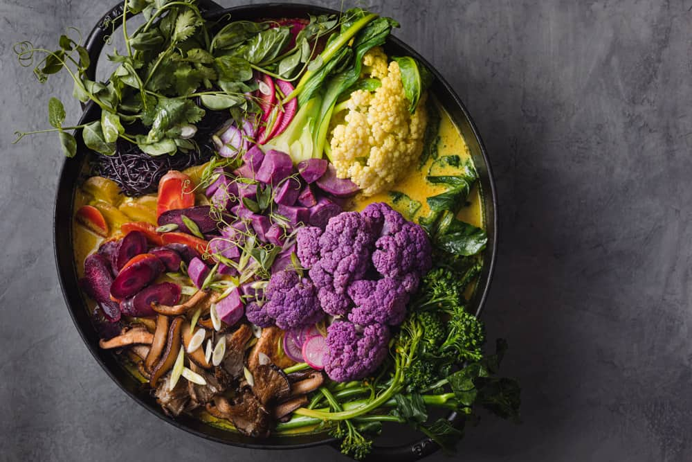 turmeric curry noodle soup with cauliflower, broccolini, sweet potatoes, mushrooms, radishes, boo chop, carrots and more! Overhead shot on a grey background.