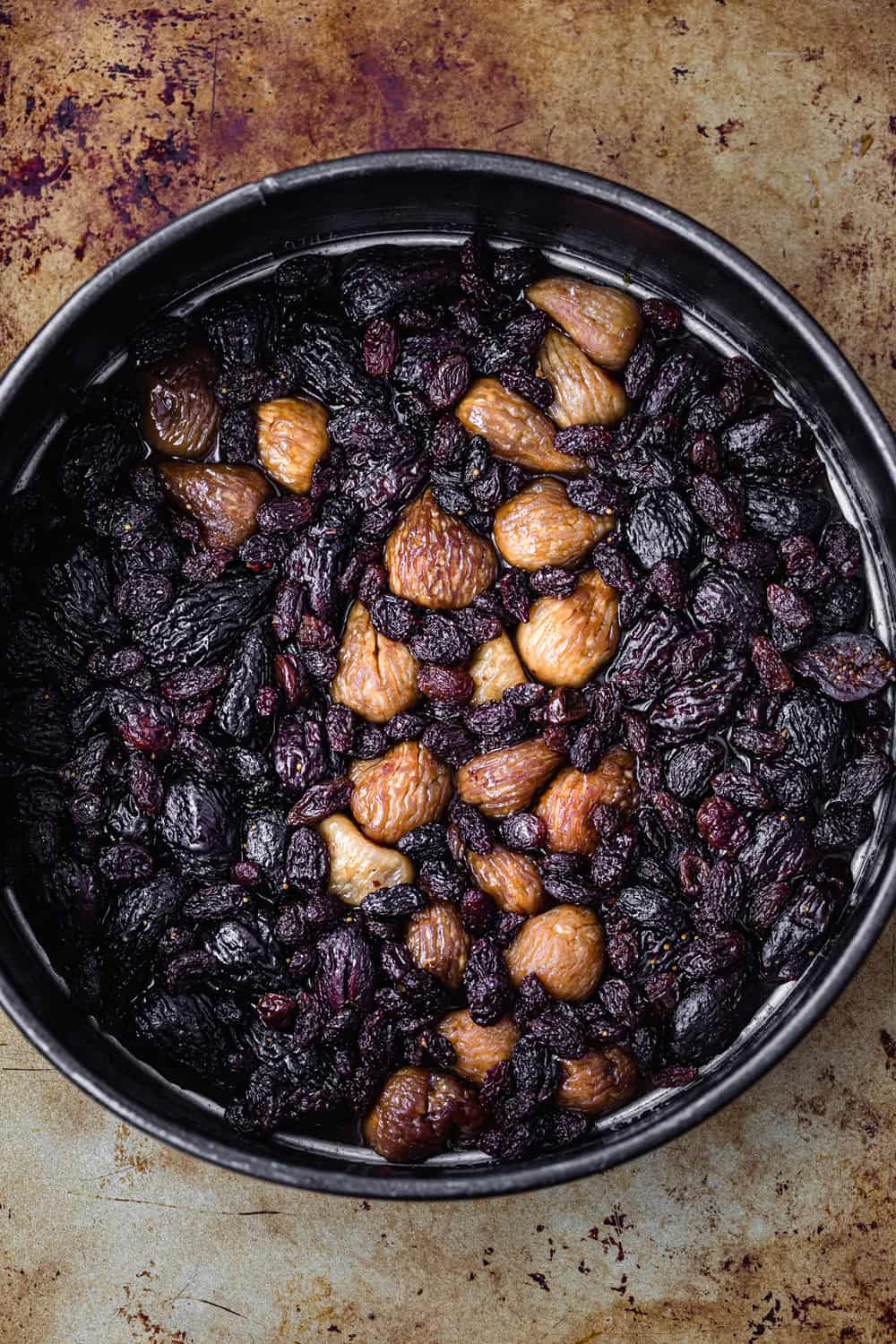 Dried figs and raisons arranged on top of caramel on springform pan; overhead shot.