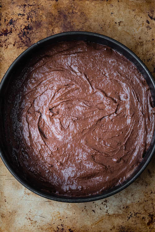 Chocolate cake batter poured into springform pan; overhead shot.