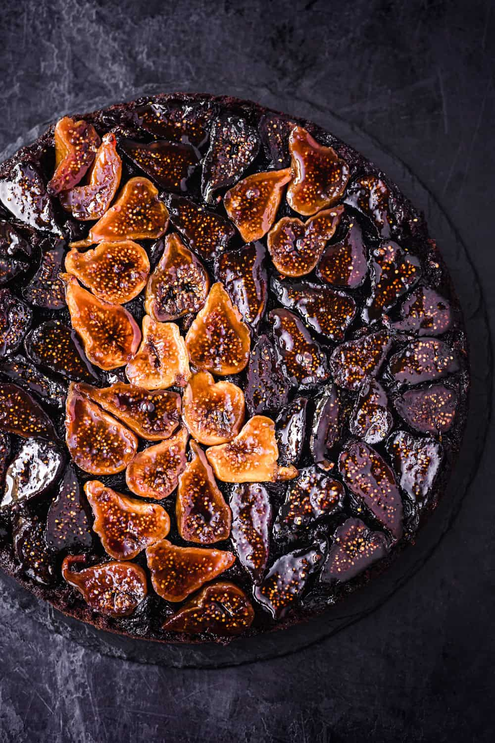 Dried fig cake all done and ready to be eaten! Overhead shot on a black background.