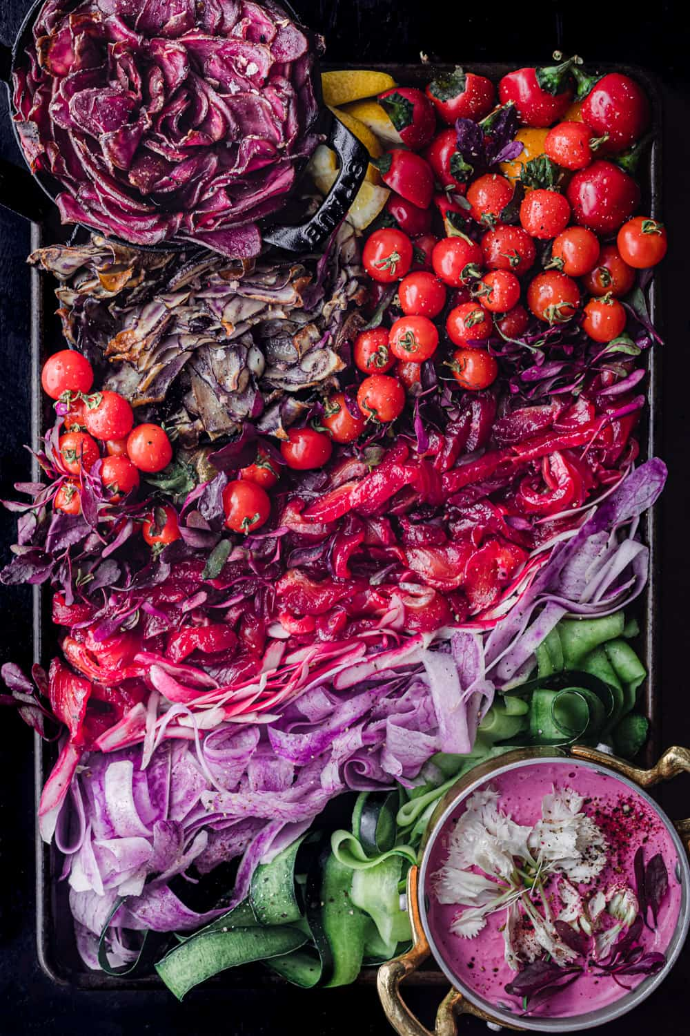 A vibrantly colorful beet cured salmon board with lots of fresh and some cooked seasonal produce; overhead shot on a black background.