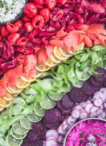 Beet cured salmon board with colorful seasonal produce arranged like a rainbow; overhead shot.