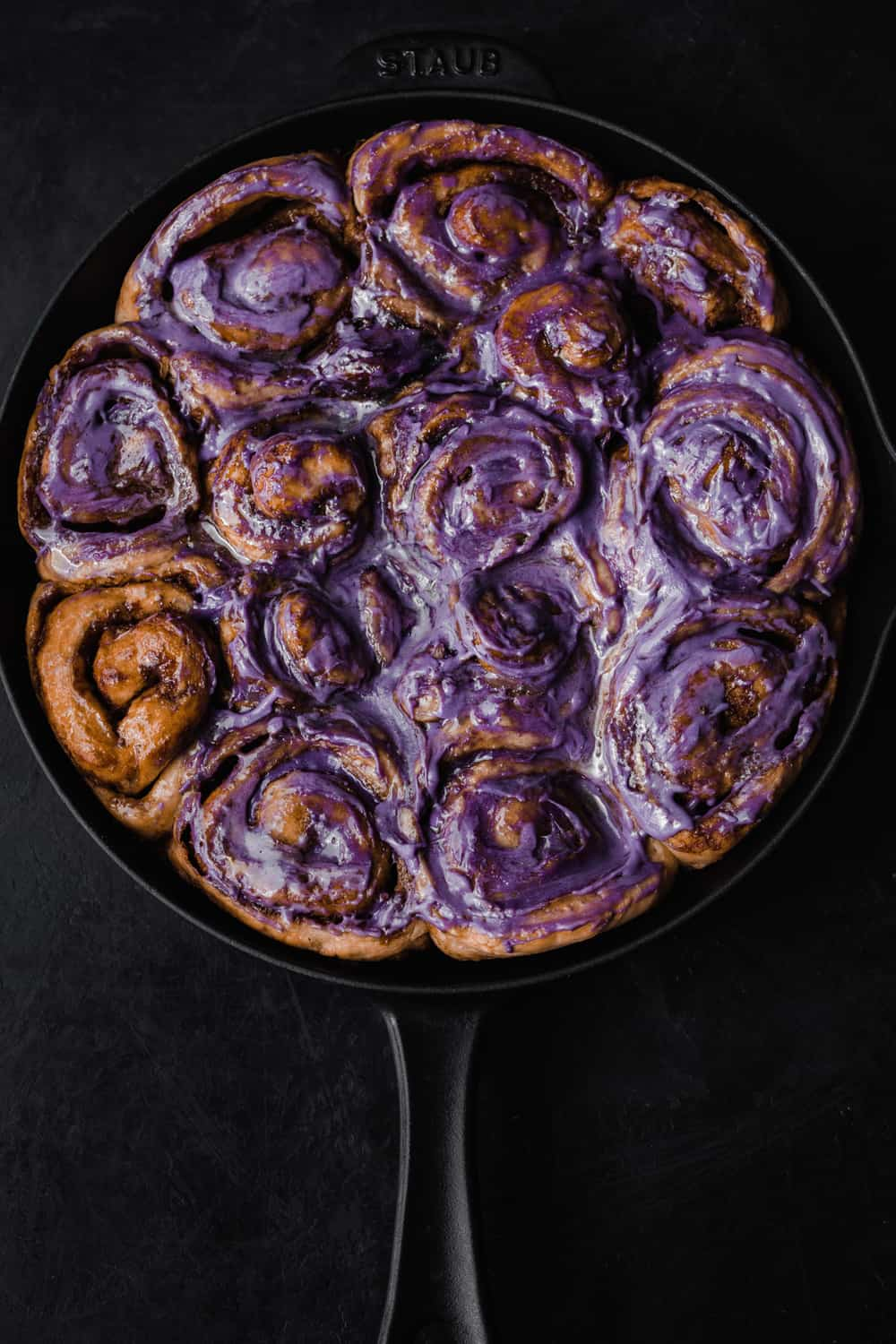Cinnamon rolls almost all frosted with a purple ube infused cream cheese icing; overhead shot on a black background.