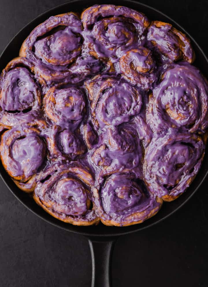 Challah Dough cinnamon rolls with an ube cream cheese frosting all done and ready to be eaten! Overhead shot on a black background.
