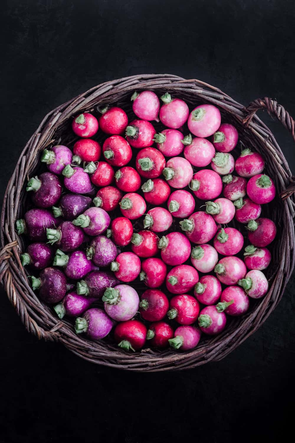 A basket filled with pink and purple radishes; overhead shot on a black background.
