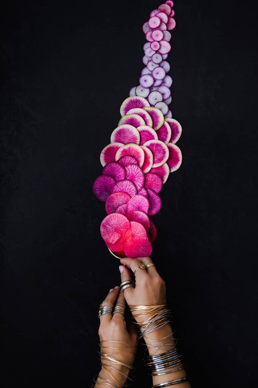 Different hues of pink and purple radishes spilling out of a large gold spoon being held by Daniela Gerson; overhead shot.