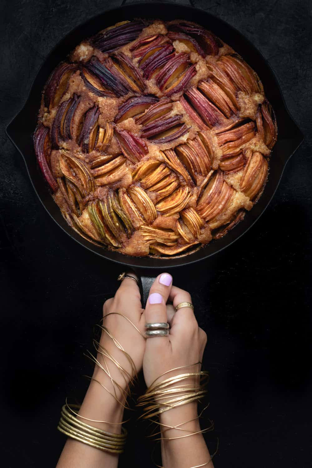 Daniela Gerson holding the finished apple cake; overhead shot on a black background.