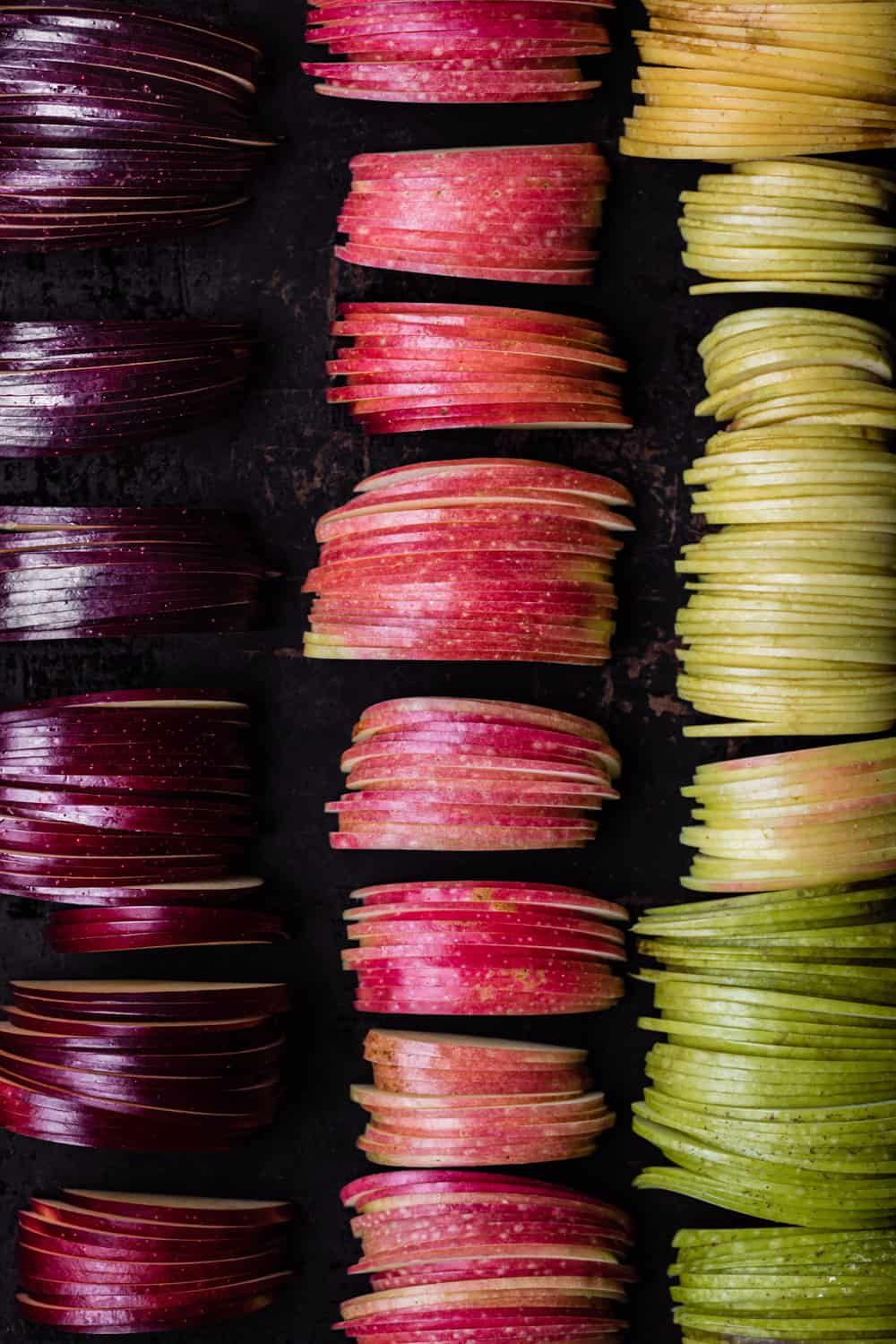 Thinly sliced apples, from purple to green, arranged cut side down, overhead shot.
