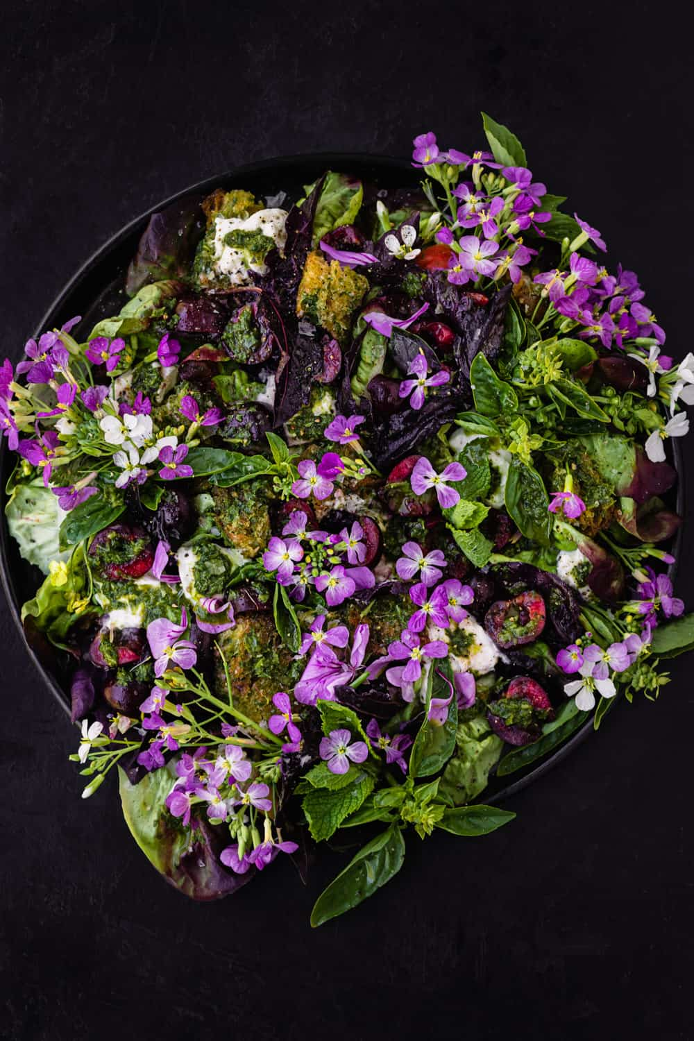 Summer cherry and fresh herb salad! with croutons, little gems, burrata and pesto vinaigrette on a black plate. Overhead shot on a black background.