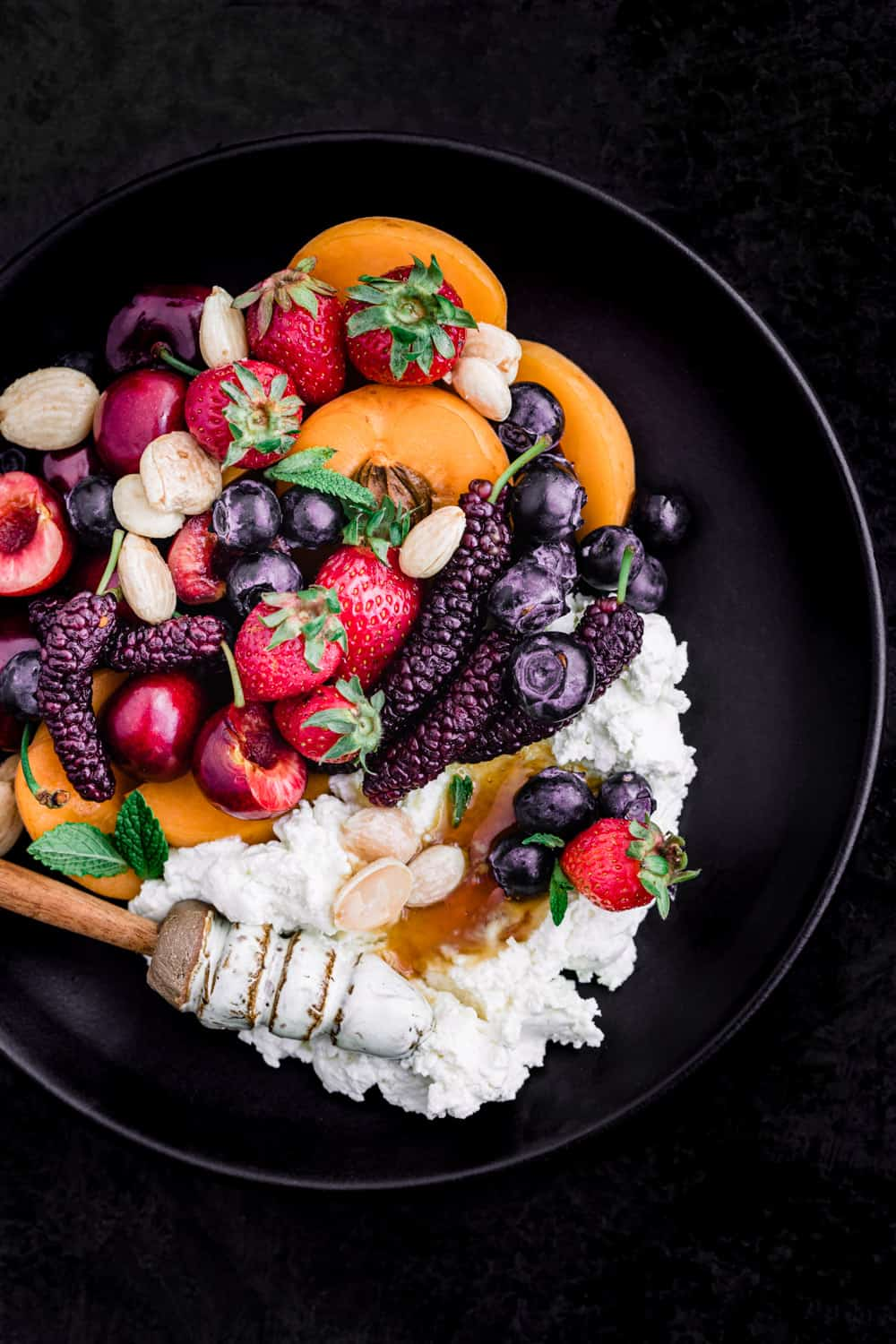 Summer fruit with fresh cheese, almonds and honey on a black plate; overhead shot on a black background.