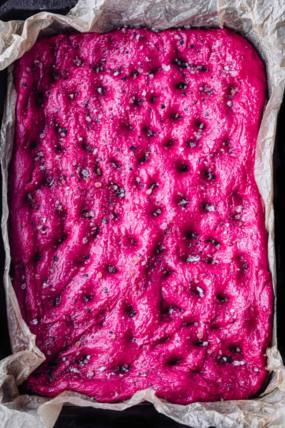Roasted Beet Focaccia dough on a baking pan sprinkled with salt; pre-oven and overhead shot.