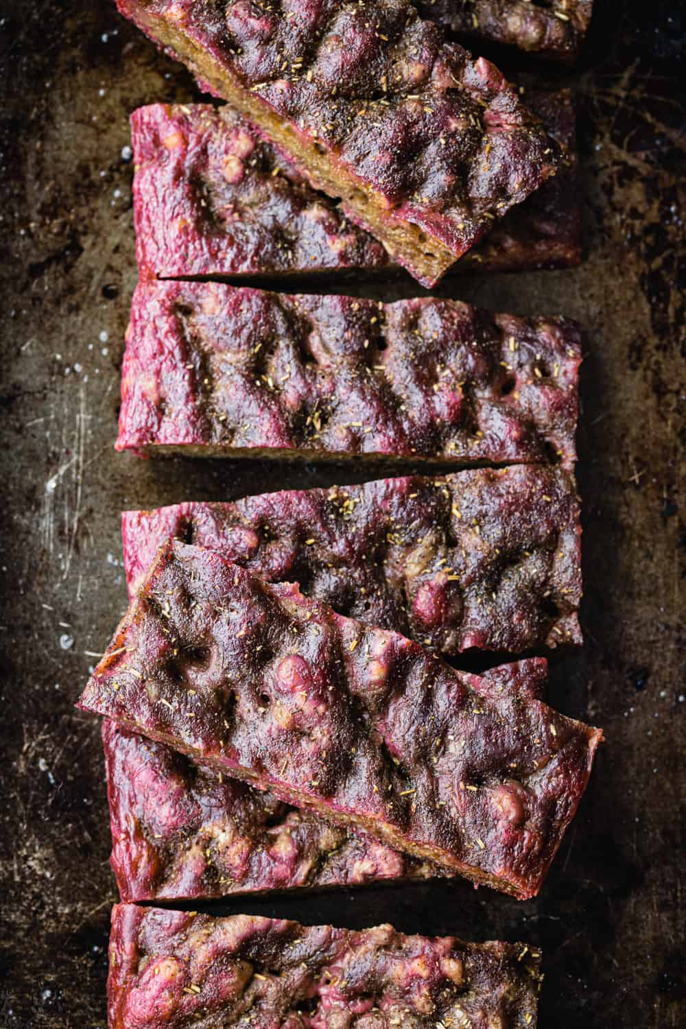 Beet focaccia on a baking sheet and cut into slices; overhead shot.