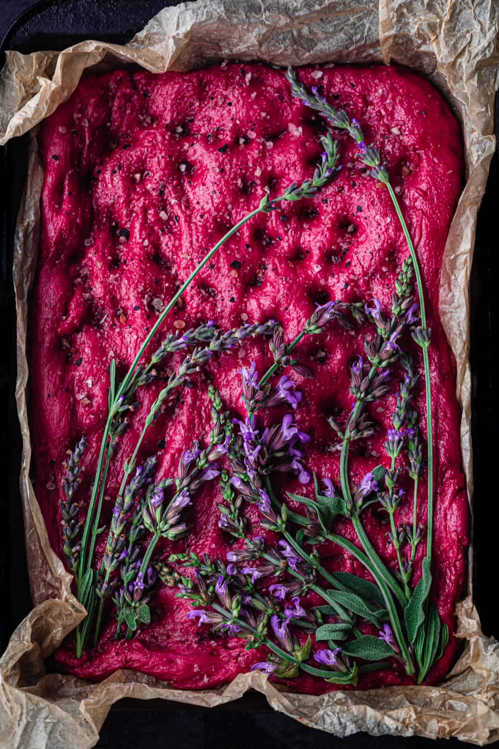 Roasted Beet Focaccia Topped with fresh lavender and sage; overhead shot.