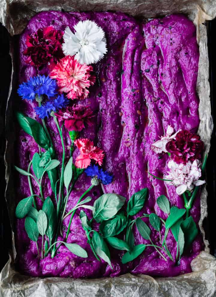 raw focaccia dough in a baking pan topped with edible flowers and herbs; overhead shot.