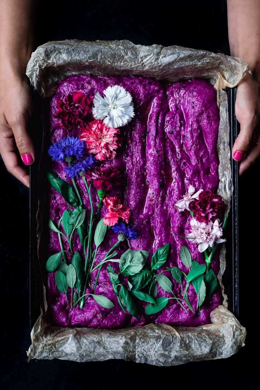 Daniela Gerson holding a pan of raw beet focaccia dough decorated like a garden; overhead shot.