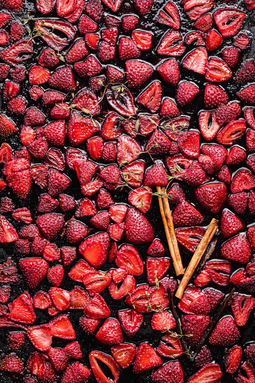 roasted strawberries just out of the oven on a baking sheet with cinnamon, vanilla beans and thyme; overhead shot.