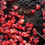 roasted strawberries on a baking sheet with a black spoon; overhead shot.