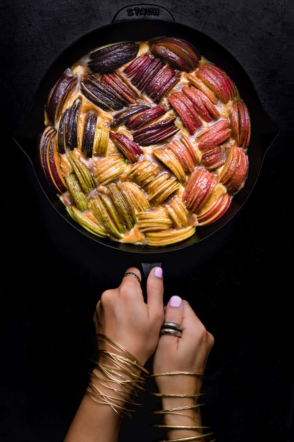 Daniela Gerson holding an cinnamon-sugar brushed apple cake; pre-oven and overhead shot on a black background.