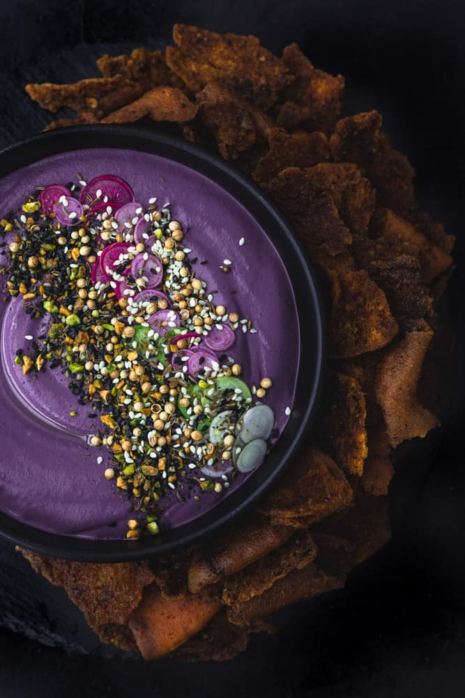 purple carrot hummus with crunchy toppings surrounded by pita chips; overhead shot