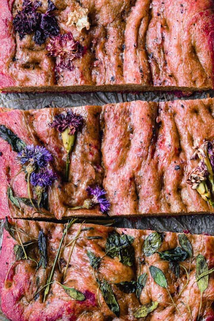 Post oven overhead roasted beet focaccia shot with edible flowers.