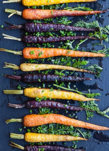 Roasted rainbow carrots topped with fresh herbs on a dark background; overhead shot