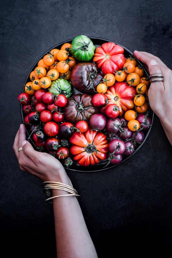 Daniela Gerson holding a black plate filled with different varieties of tomato that together create a rainbow!