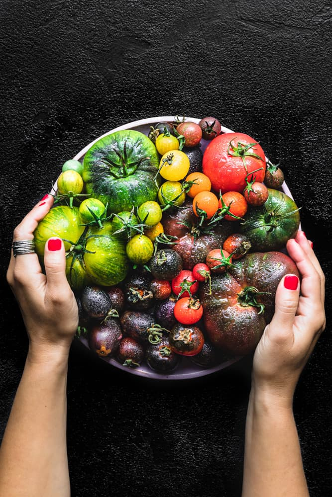 Daniela Gerson holding a pink plate filled with tomatoes in all the colors of the rainbow.