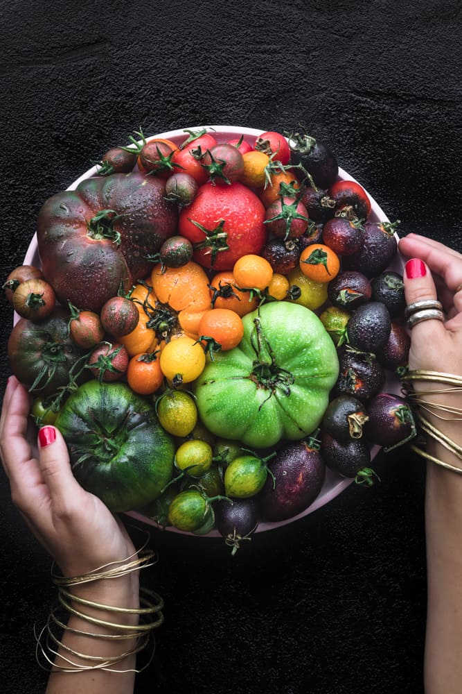 Daniela Gerson holding a plate filled with heirloom and cherry tomatoes in all the colors of the rainbow.