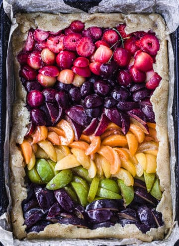 Pre-oven and overhead shot of a very colorful stone fruit galette with red, orange, yellow, green and purple colors of different stone fruits arranged like a rainbow